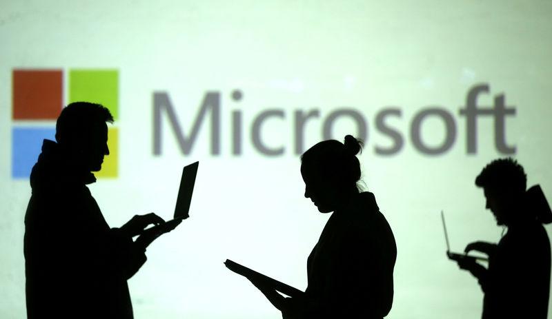 © Reuters. Силуэты пользователей с ноутбуками на фоне логотипа Microsoft