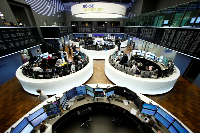 © Reuters. FILE PHOTO: Traders work at their desks in front of the German share price index, DAX board, at the stock exchange in Frankfurt