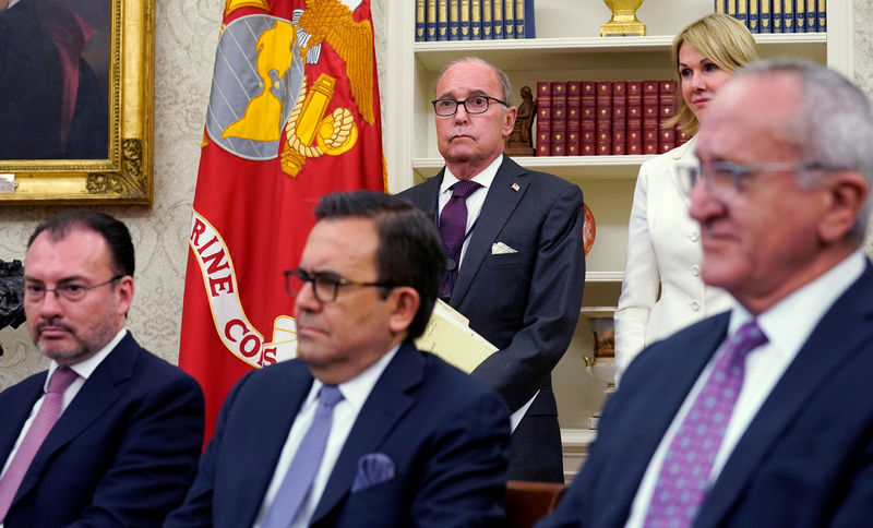 © Reuters. White House aides look on as Trump announces deal on NAFTA at the White House in Washington
