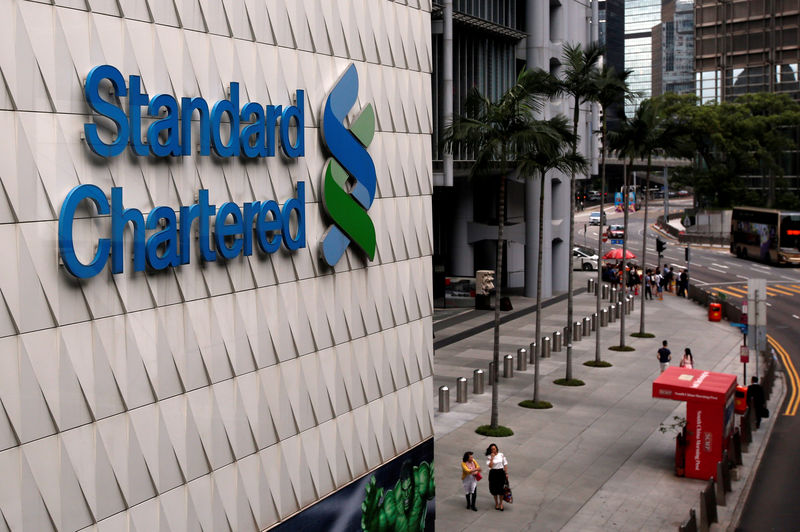 © Reuters. FILE PHOTO: People walk outside the main branch of Standard Chartered in Hong Kong