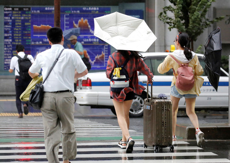 © Reuters. Passersby using umbrellas struggle against a heavy rain and wind in front of an electronic stock quotation board as Typhoon Shanshan approaches Japan's mainland in Tokyo