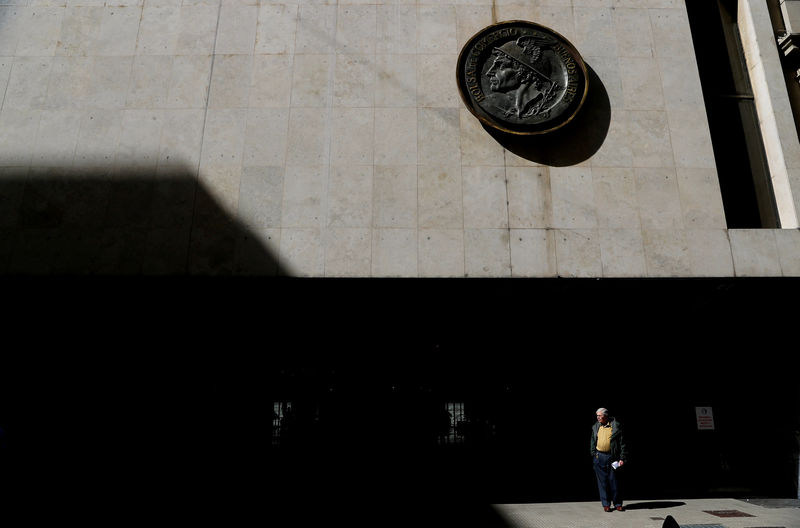 © Reuters. A man stands outside the Stock Exchange building in Buenos Aires' financial district