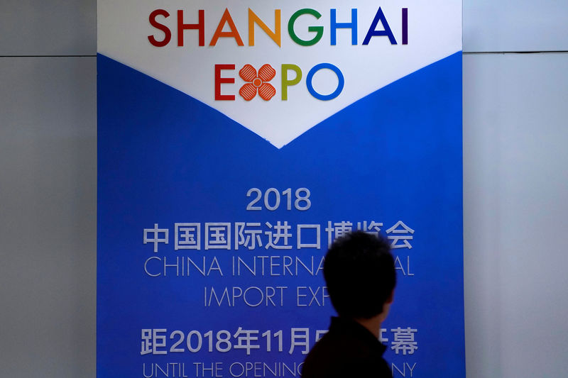 © Reuters. FILE PHOTO: A man walks past a countdown board of the China International Import Expo in Shanghai