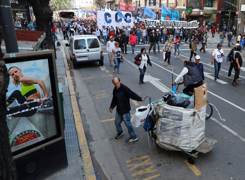 © Reuters. A garbage recycler pushes his cart as demonstrators march during a protest against the government's economic measures in Buenos Aires