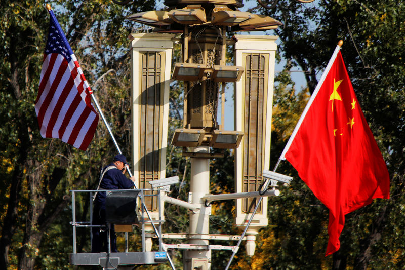 © Reuters. FILE PHOTO: A worker places U.S. and China flags near the Forbidden City ahead of a visit by U.S. President Donald Trump to Beijing, in Beijing