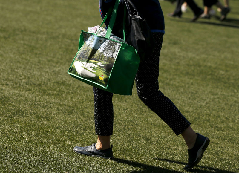 © Reuters. FILE PHOTO: Woman walks with a full shopping bag during the Drive, Chip and Putt National Finals at the Augusta National Golf Course in Augusta