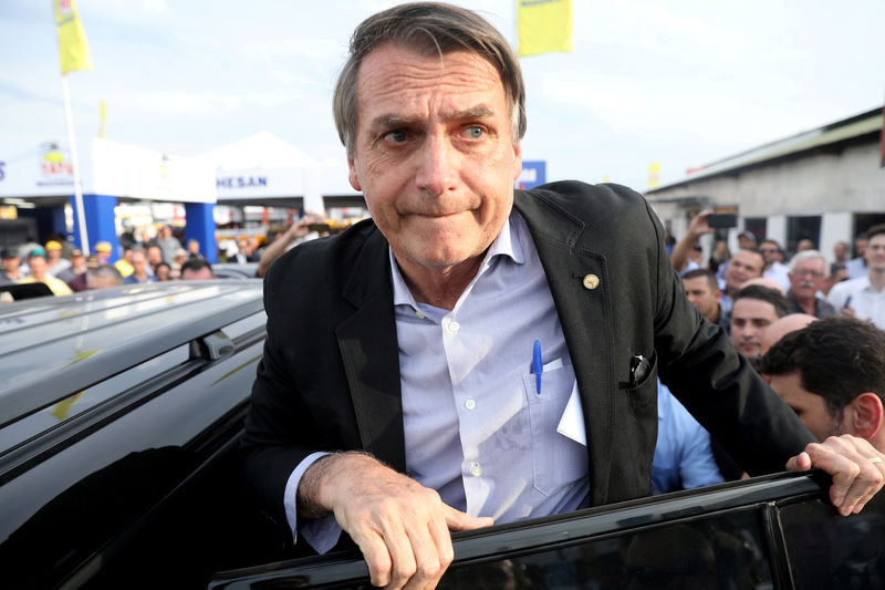 © Reuters. FILE PHOTO: Presidential candidate Jair Bolsonaro leaves an agribusiness fair in Esteio