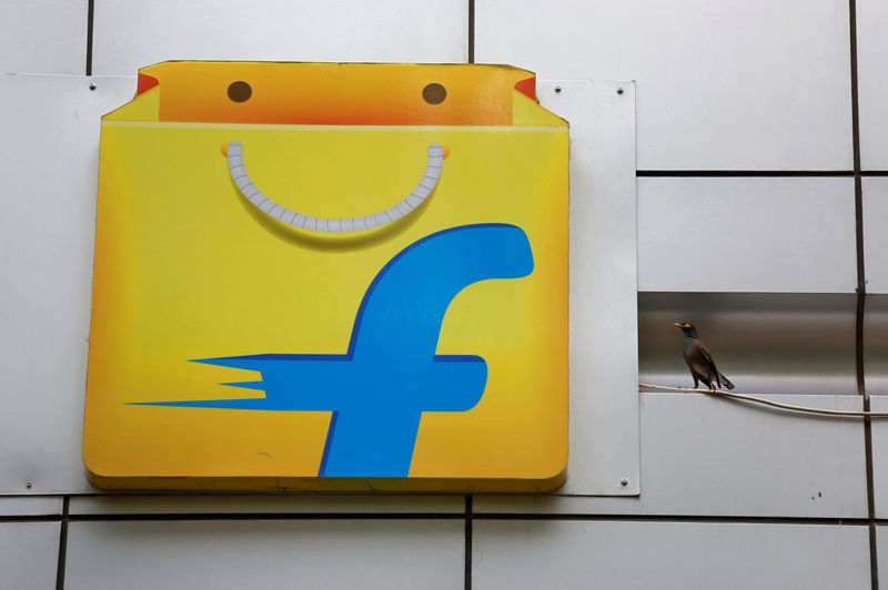 © Reuters. A Common myna sits next to the logo of India's e-commerce firm Flipkart installed on the company's office in Bengaluru