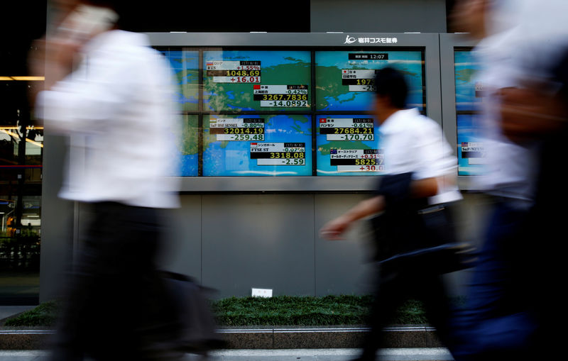 © Reuters. FILE PHOTO: People walk past an electronic board showing Japan's Nikkei average outside a brokerage at a business district in Tokyo