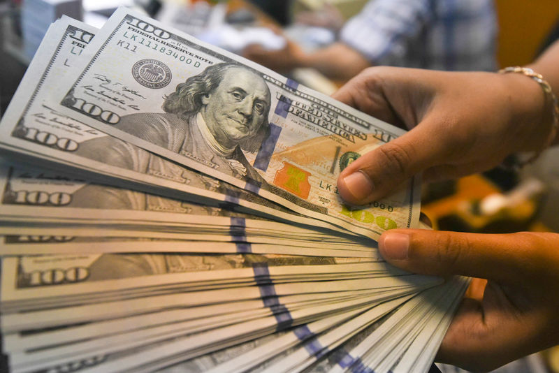 © Reuters. An employee shows U.S. dollars banknotes at a money changer in Jakarta