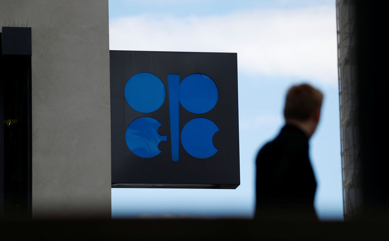 © Reuters. A person passes the OPEC logo in front of OPEC's headquarters in Vienna