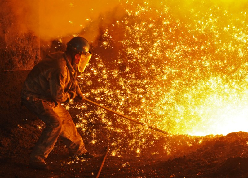 © Reuters. An employee works next to molten iron at a steel mill in Dalian