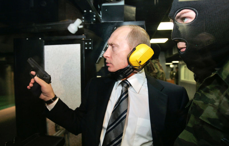 © Reuters. FILE PHOTO: Russian President Putin and a masked security officer stand at a shooting gallery in Moscow