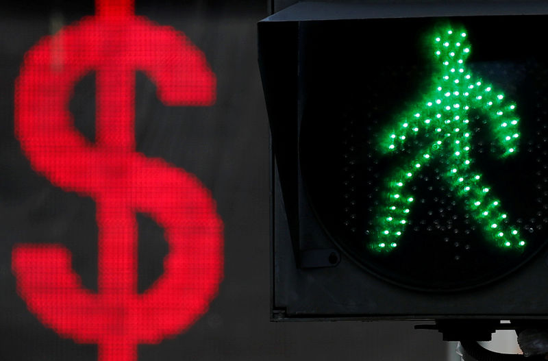 © Reuters. FILE PHOTO: The U.S. dollar sign is seen on an electronic board next to a traffic light in Moscow
