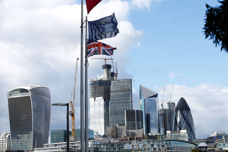 © Reuters. Flags flutter in the wind with the financial district in the background, in London