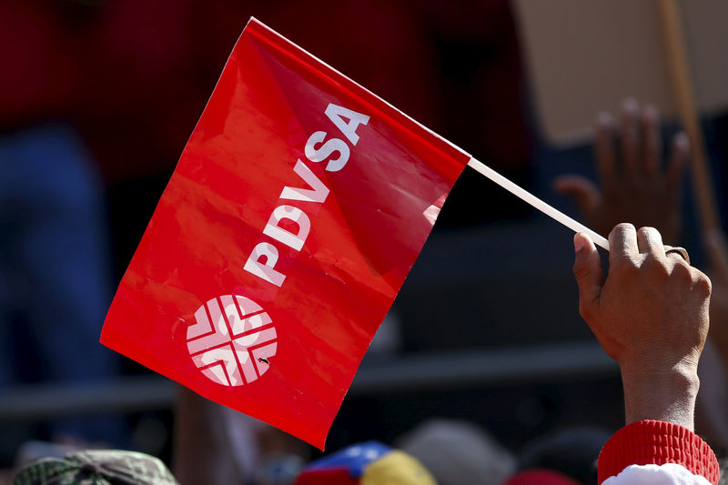 © Reuters. FILE PHOTO: A worker of the Venezuelan state oil company PDVSA holds a flag with the company logo, during a meeting with Venezuela's President Nicolas Maduro outside Miraflores Palace in Caracas