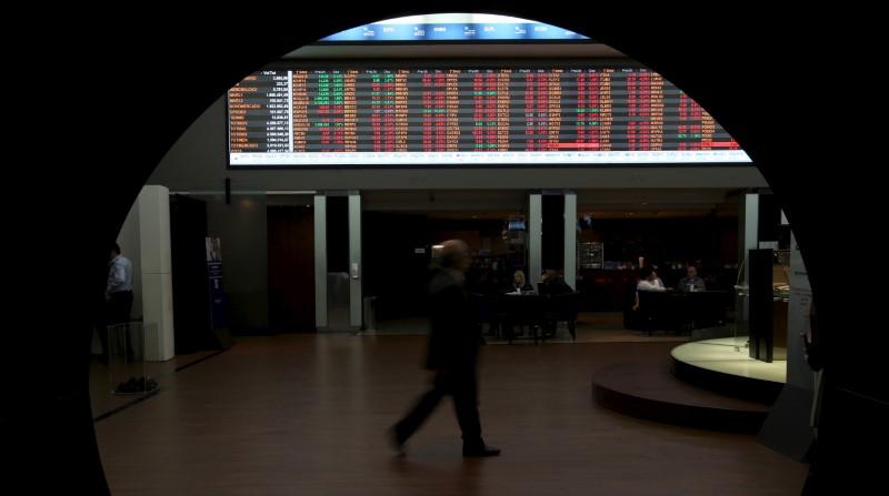 © Reuters. Homem passa por gráfico de cotações na Bovespa
