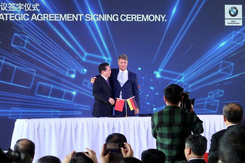© Reuters. Harald Krueger, BMW Chief Executive hugs Chen Qiufa, Communist Party Secretary of Liaoning province for a photo during a signing ceremony inside the BMW Brilliance Plant Tiexi, in Shenyang