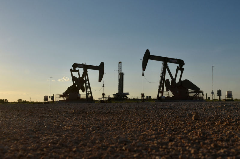 © Reuters. FILE PHOTO: Pump jacks operate in front of a drilling rig in an oil field in Midland