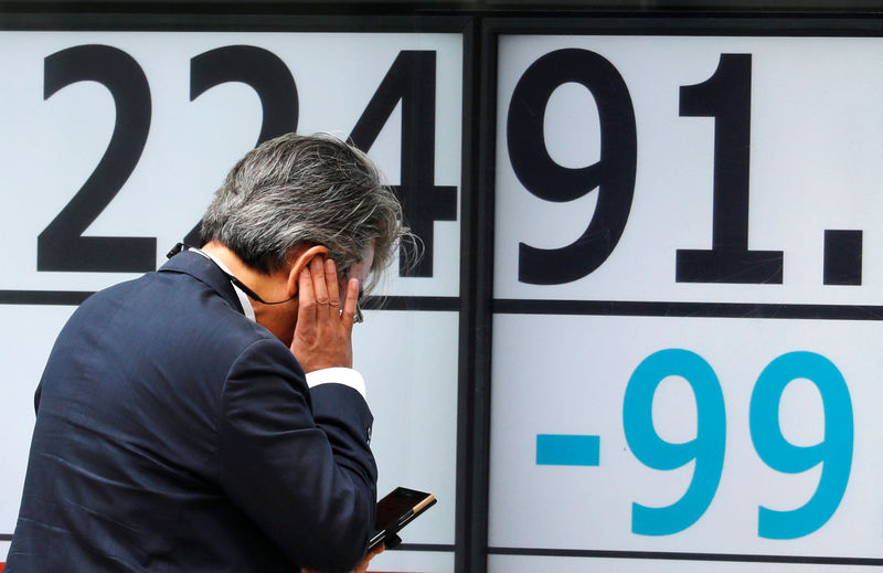 © Reuters. A man uses a mobile phone in front of an electronic board showing Japan's Nikkei average outside a brokerage in Tokyo