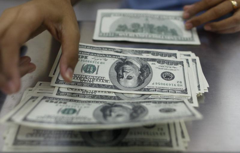 © Reuters. Долларовые банкноты в пункте обмена валют в Янгоне