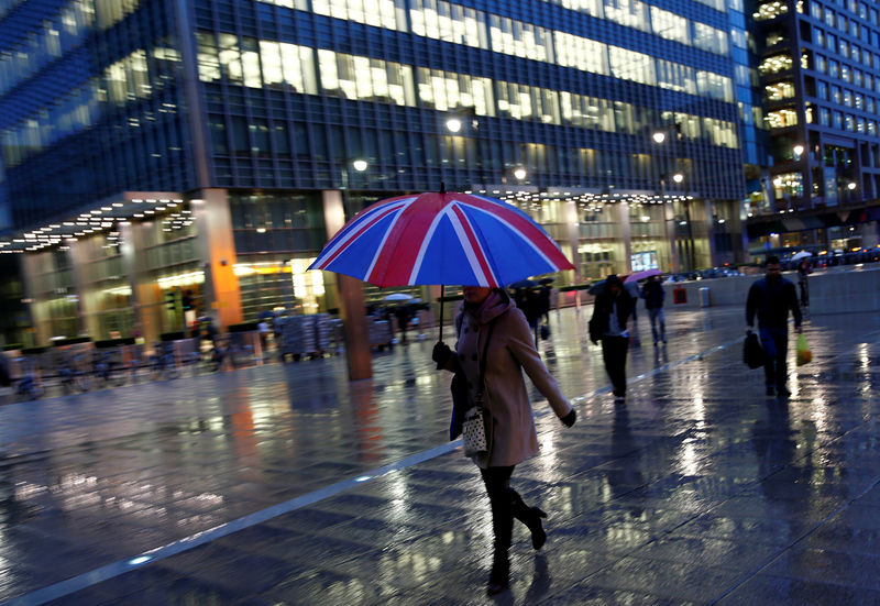 © Reuters. FILE PHOTO: Workers walk in the rain at the Canary Wharf business district in London