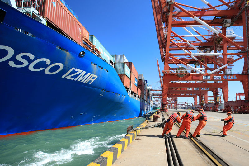 © Reuters. Workers help to dock a China Ocean Shipping Company (COSCO) container ship at a port in Qingdao