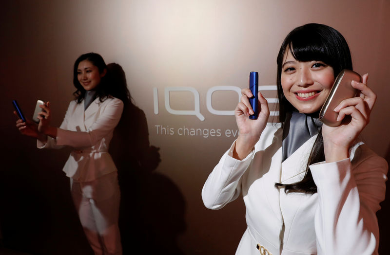 © Reuters. Promotional staff pose with Philip Morris' IQOS 3  (R) and IQOS 3 MULTI devices after their launching event in Tokyo
