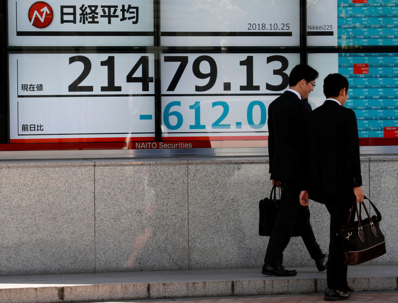 © Reuters. Men walk past an electronic board showing Japan's Nikkei average outside a brokerage in Tokyo