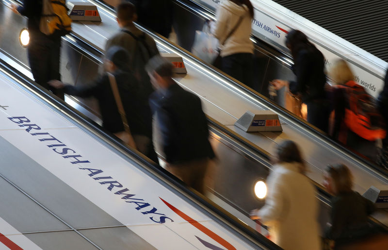 © Reuters. FILE PHOTO: Commuters pass a British Airways advert on the tube at Canary Wharf
