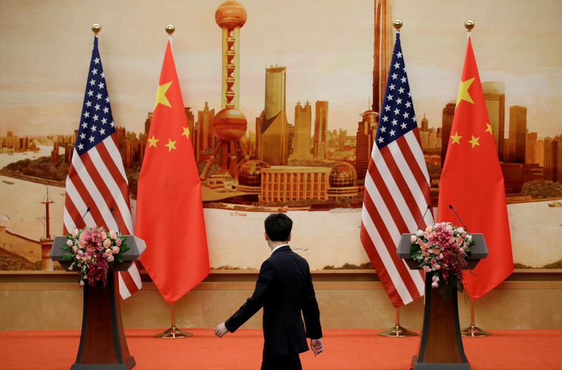 © Reuters. FILE PHOTO: A staff member walks past U.S. and Chinese flags placed for a joint news conference in Beijing