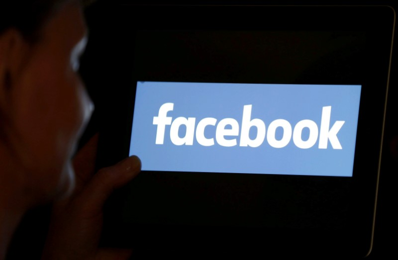 © Reuters. FILE PHOTO: A woman looks at the Facebook logo on an iPad in this photo illustration