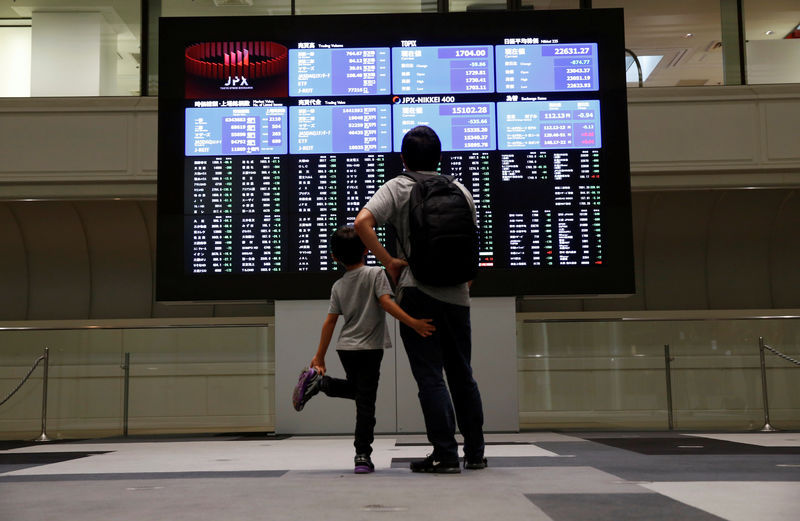 © Reuters. Visitors look at a stock quotation board at Tokyo Stock Exchange in Tokyo
