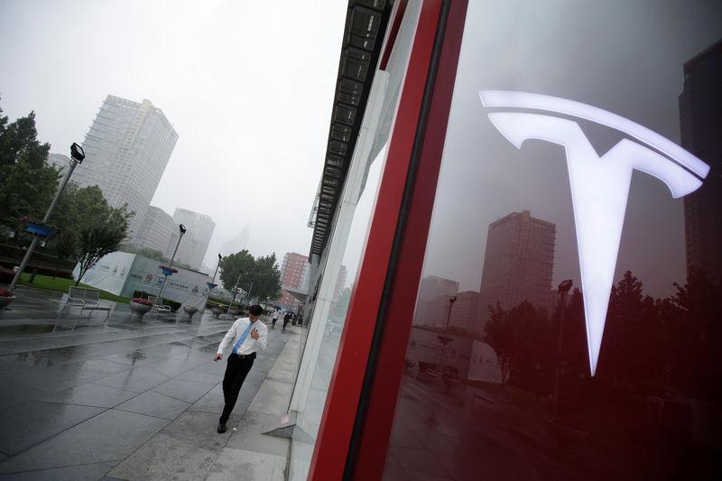 © Reuters. A man walks near a logo of Tesla outside its China headquarters in Beijing