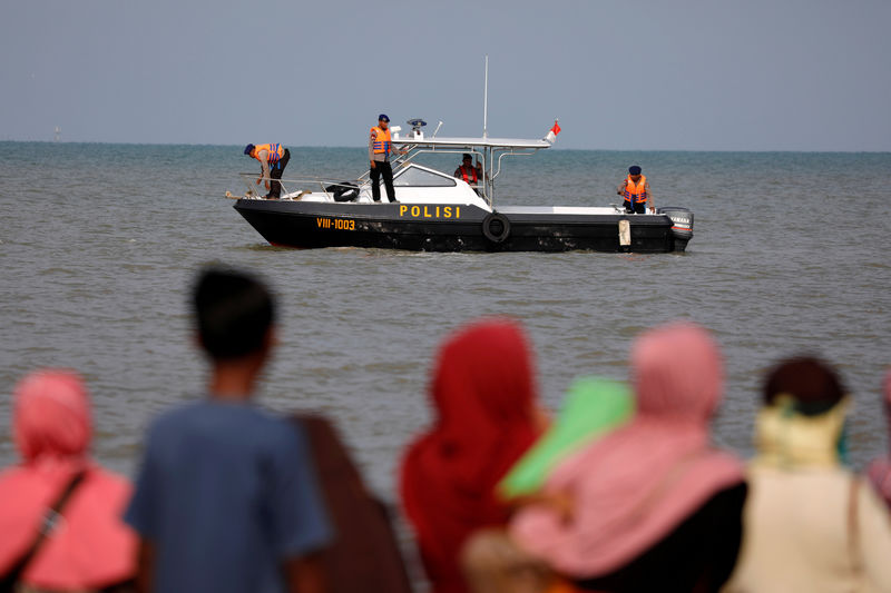 © Reuters. People watch rescue team members on a boat before they head to the Lion Air plane sea crash location in the north coast of Karawang regency