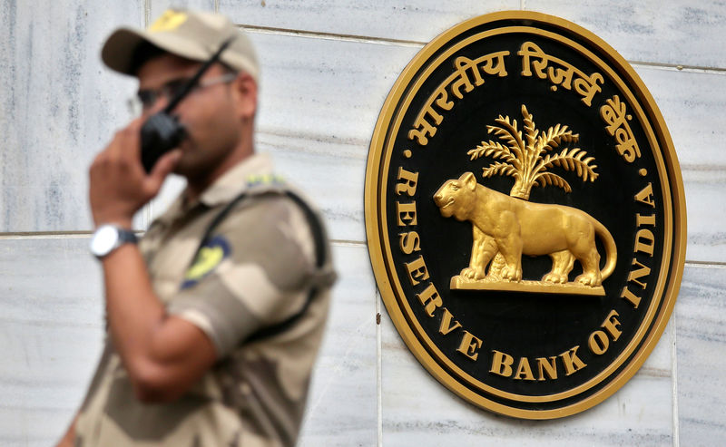 © Reuters. FILE PHOTO: A guard stands next to the {{0|Reserve Bank of India}} (RBI) logo outside its headquarters in Mumbai
