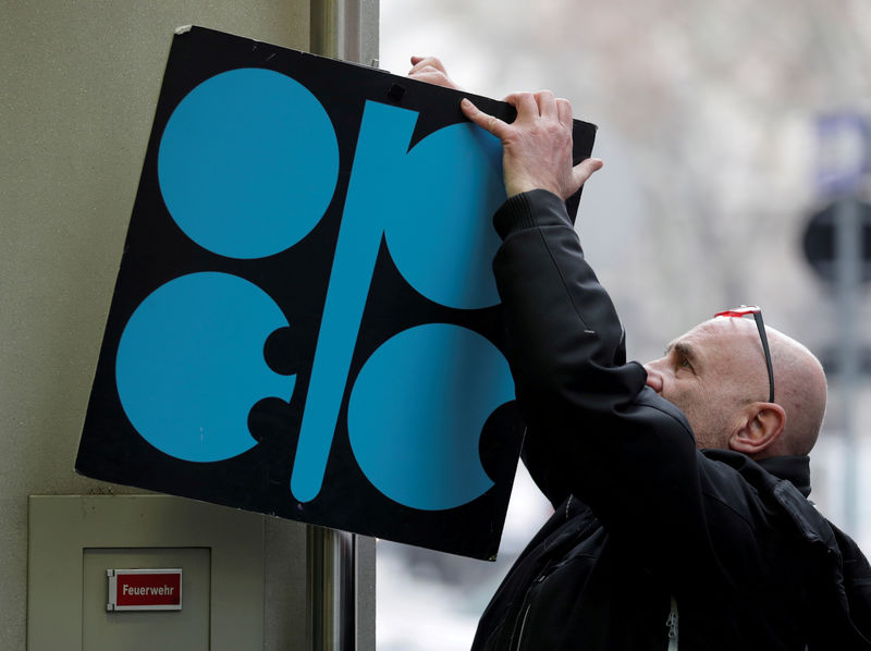 © Reuters. FILE PHOTO: A man fixes a sign with OPEC's logo next to its headquarters in Vienna
