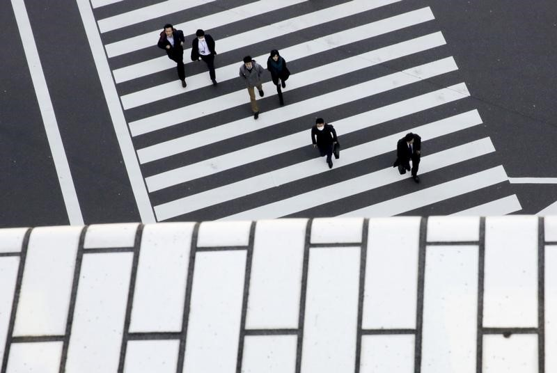 © Reuters. FILE PHOTO - People cross a street in a business district in Tokyo