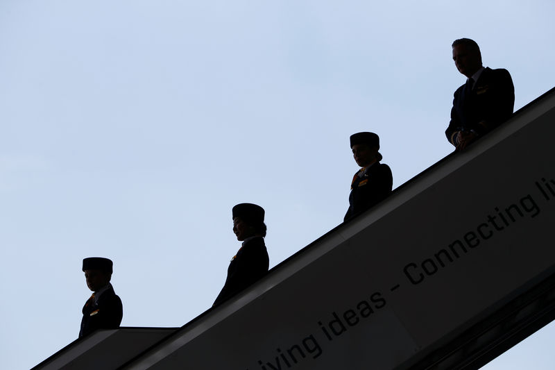 © Reuters. Steward and stewardesses are silhouetted before the baptism of the 10th Lufthansa A350 to the name