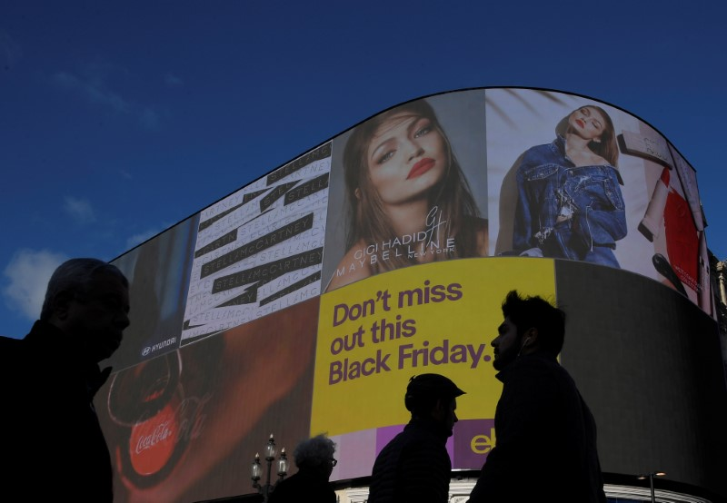 © Reuters. Shoppers are seen walking past the electronic billboard at Piccadilly Circus, showing retail adverts incuding one for 'Black Friday' in London, Britain