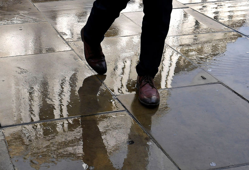 © Reuters. A worker walks over paving stones with the Bank of England seen reflected in them, in the City of London, Britain