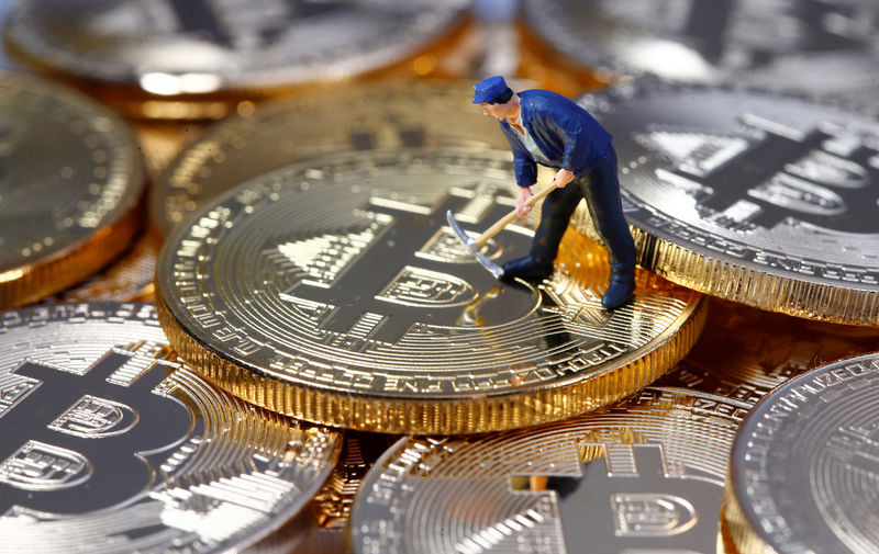 © Reuters. FILE PHOTO - A small toy figure is seen on representations of the Bitcoin virtual currency in this illustration picture