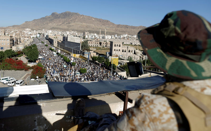© Reuters. FILE PHOTO: Houthi militant sits guard on the roof of a building overlooking fellow Houthis rallying to denounce the rapid devaluation of the Yemeni Rial in Sanaa, Yemen