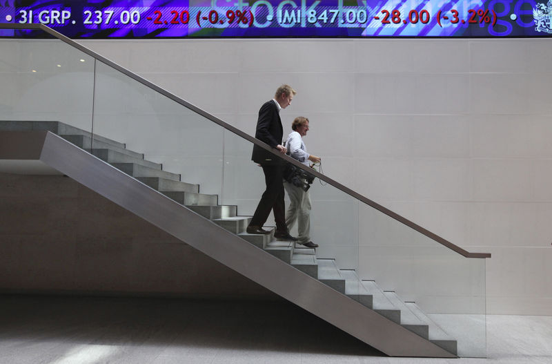 © Reuters. People walk down a staircase underneath a stock ticker inside the London Stock Exchange