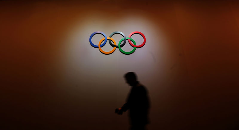© Reuters. FILE PHOTO: A man walks past the Olympic Rings as he walks out of the 133rd IOC session in Buenos Aires