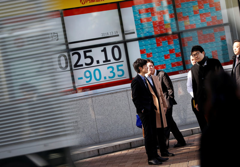 © Reuters. Men stand in front of a stock quotation board outside a brokerage in Tokyo