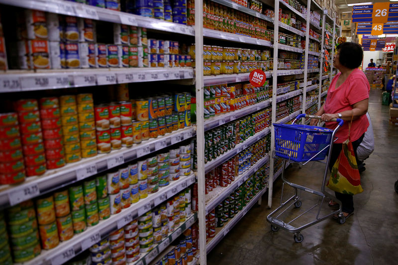 © Reuters. Woman scans the selection of canned goods at a grocery store in Makati