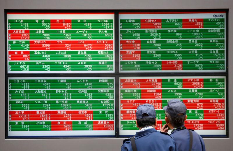 © Reuters. Men look at stock prices before brokerage in Tokyo