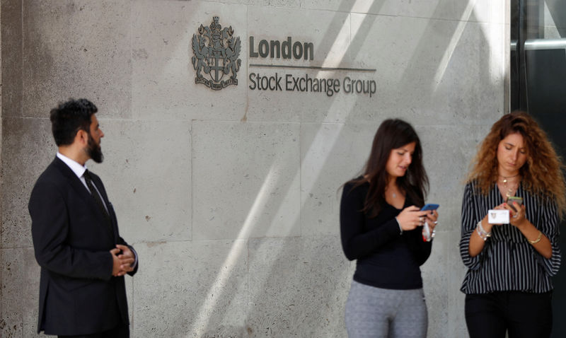© Reuters. People check their mobile phones as they stand outside the entrance of the London Stock Exchange in London
