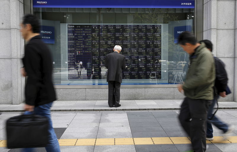 © Reuters. Man looks at a stock quotation board outside a brokerage in Tokyo